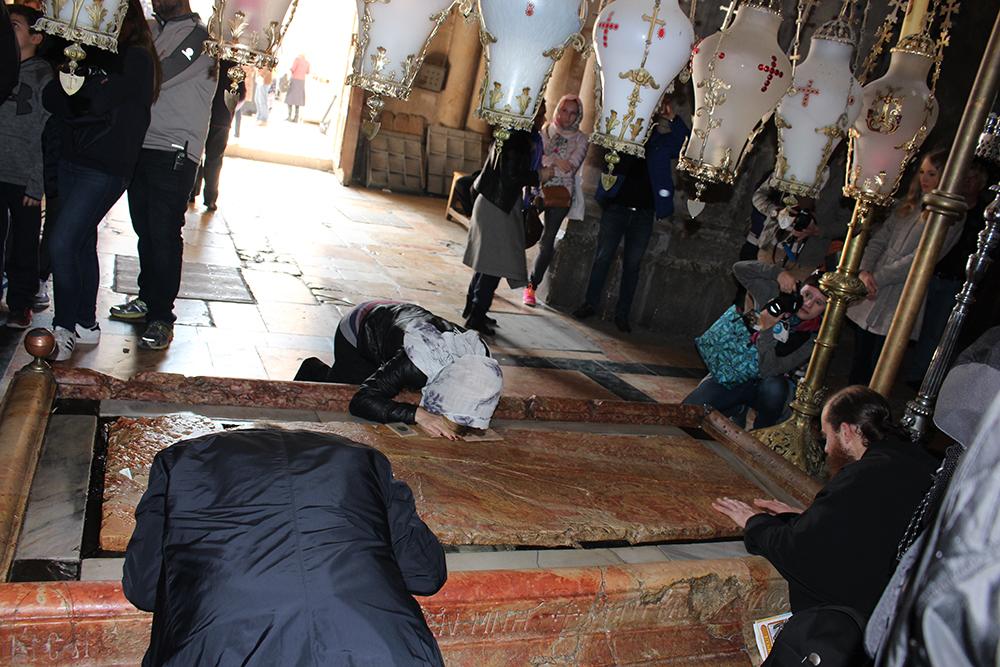 Personnes qui se recueille sur la pierre tombale de Jésus