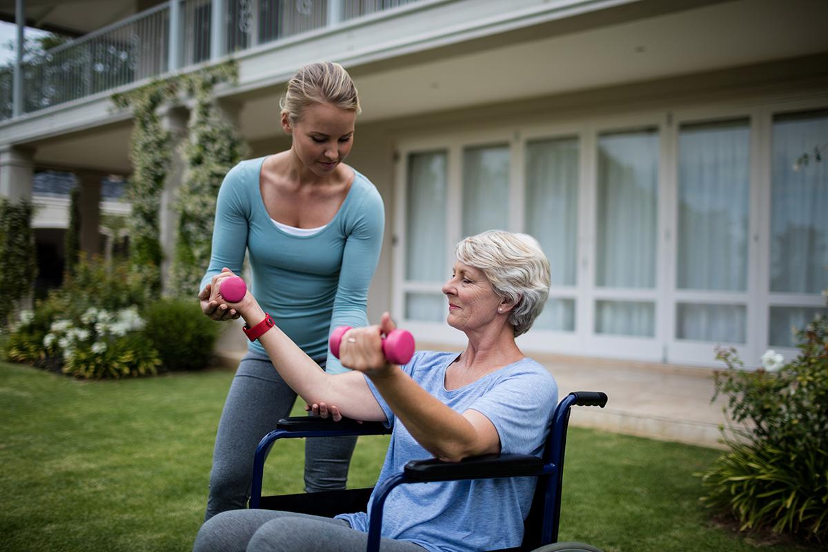 Coach qui aide une senor pour ses exercices physiques.