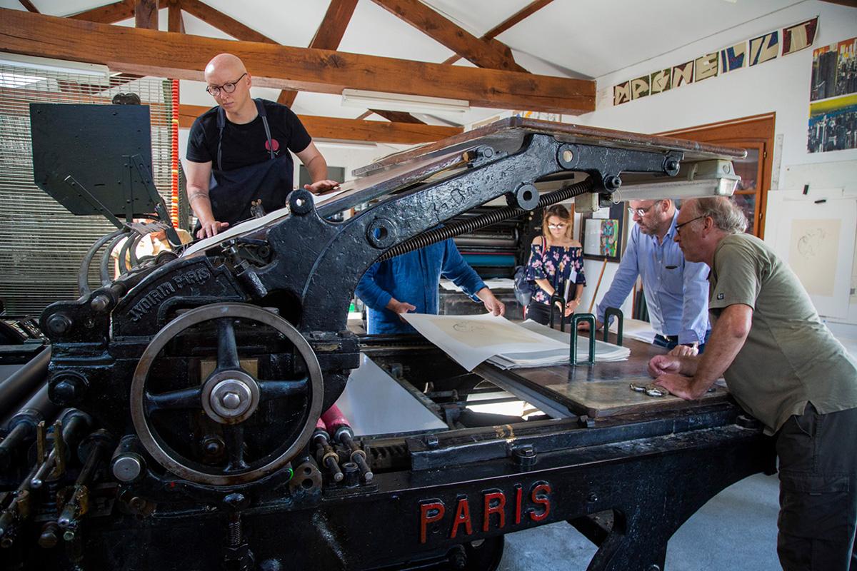 Dans l'atelier de lithographie, l'équipe s'active sur une des presses Voirin.