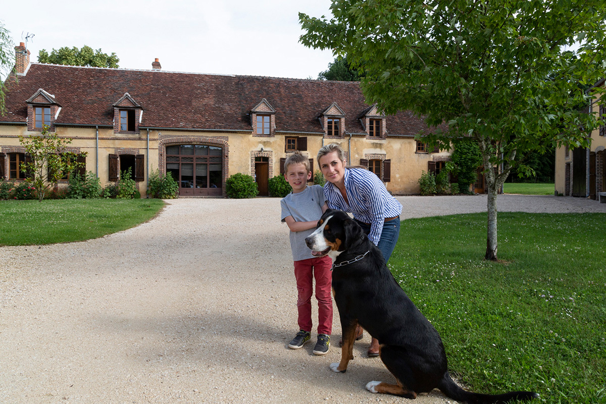 Béatrice Vola, avec un de ses jumeaux, a restauré le Hameau de la Fausse Sauge avec beaucoup de patience et de goût. ©Caroline Paux