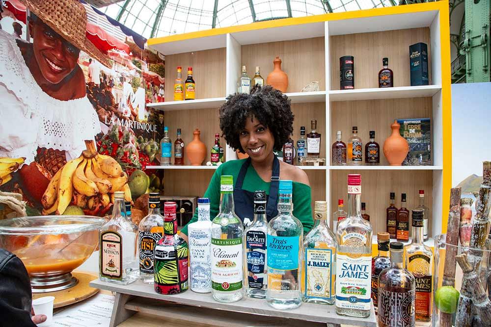 Le sourire naturel et accueillant d'une des hôtesses au stand de la Martinique pour présenter les marques typiques des rhums AOC…