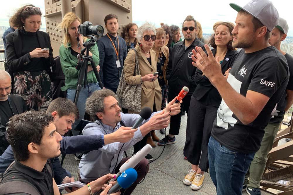 Saype, très sollicité par la presse, lors de la présentation de l'œuvre au 2e étage de la Tour Eiffel, vendredi 14 juin.