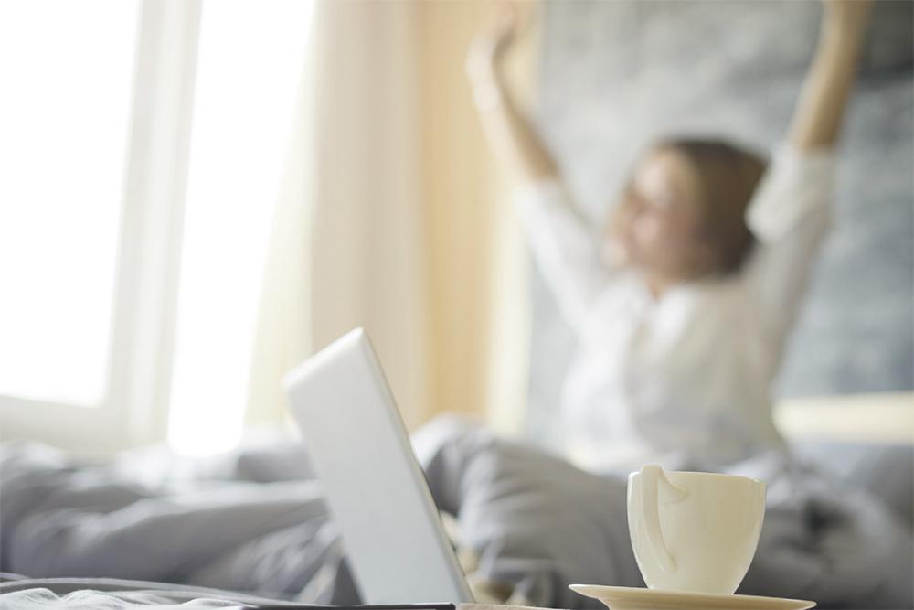 SOS AROMA femme au lit avec son ordinateur.