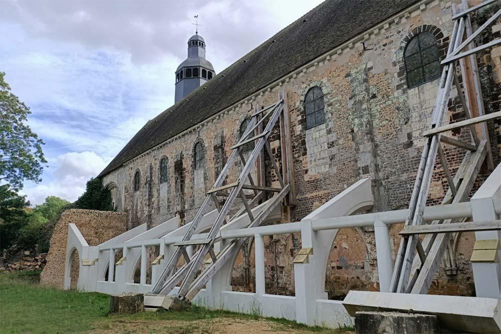 L'église abbatiale côté nord, avec les contreforts en béton qui soutiendront la galerie reconstituée du cloître.