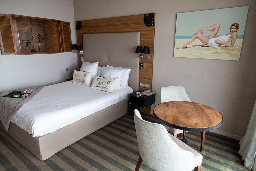 Des persiennes ouvertes sur la chambre dans la salle de bains… Un tableau de Rod Stribley pour mieux vous accueillir.