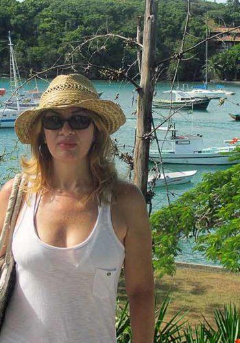 Femme au soleil avec lunettes solaires et chapeau de paille