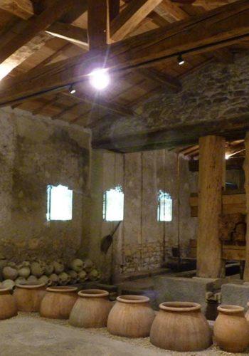 Grande salle avec les amphores de fermentation et, au fond, le pressoir romain reconstitué