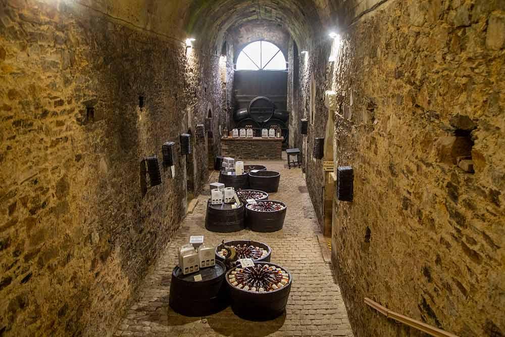 Passage dans le cellier sous l'immense voute de pierres.