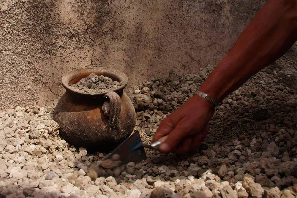 Une marmite en bronze émerge des lapilli lors de l'excavation.