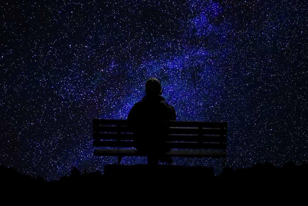 Homme assis sur un banc regarde le ciel et les étoiles