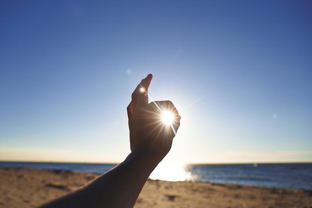 Main face à l'océan qui capte la lumière