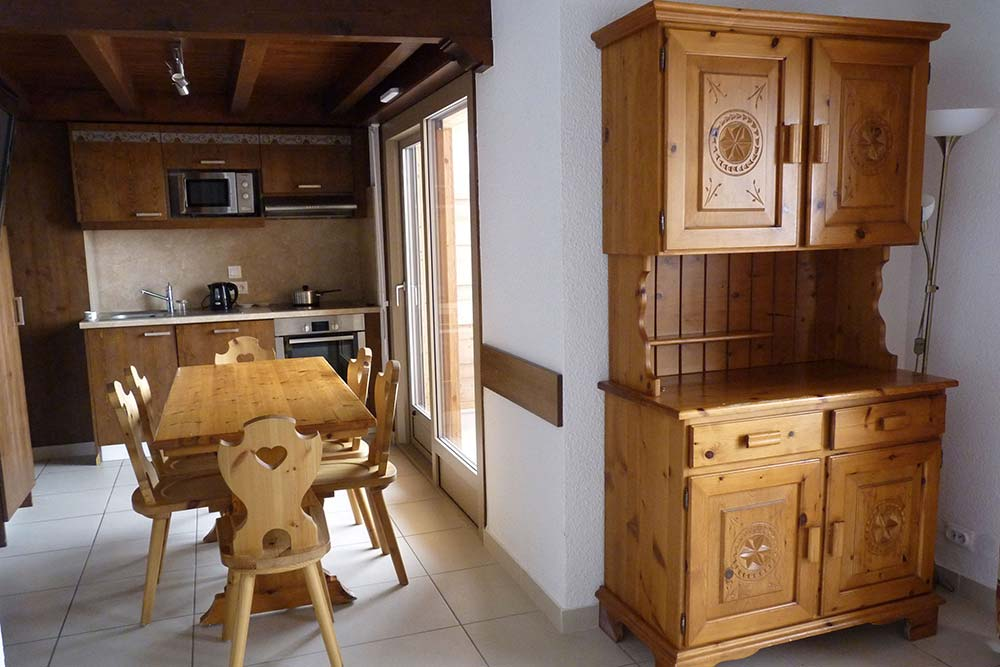 VVF - Le séjour de style savoyard avec son vaisselier et sa cuisine (Duplex)