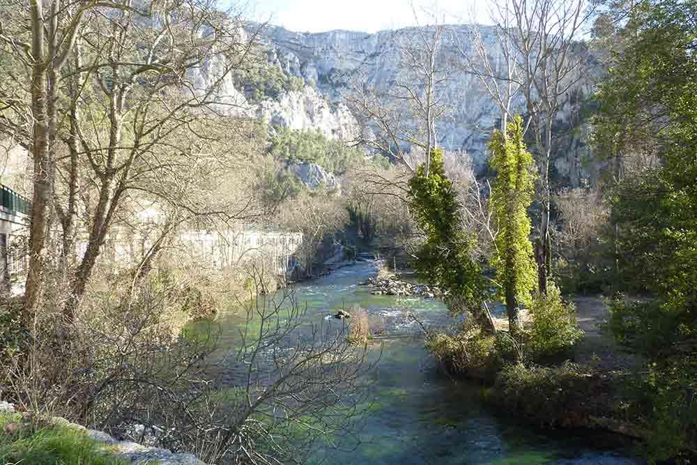 Fontaine-de-Vaucluse: les eaux turquoise de la Sorgue et, au fond, les falaises