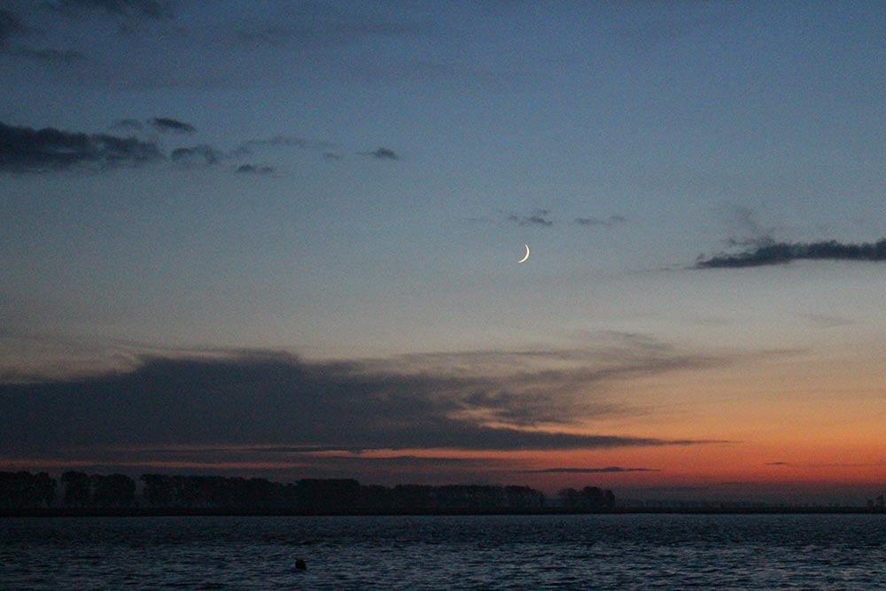 La lune fait son apparition, le ciel devient rouge et la mer noire