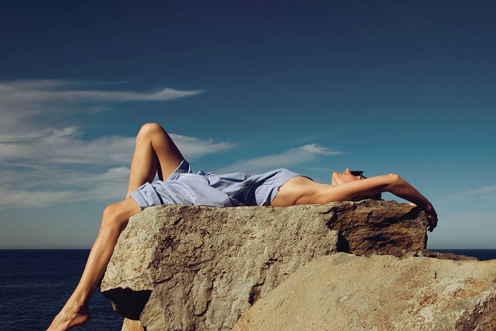 Jeune femme allongée sur un rocher